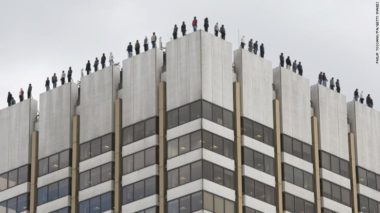 84 Male Figures, Poised to Jump from London Rooftop
